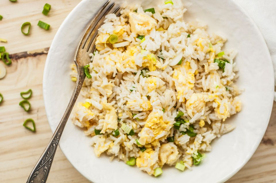 Basic fried rice with egg and green onions in a bowl with fork
