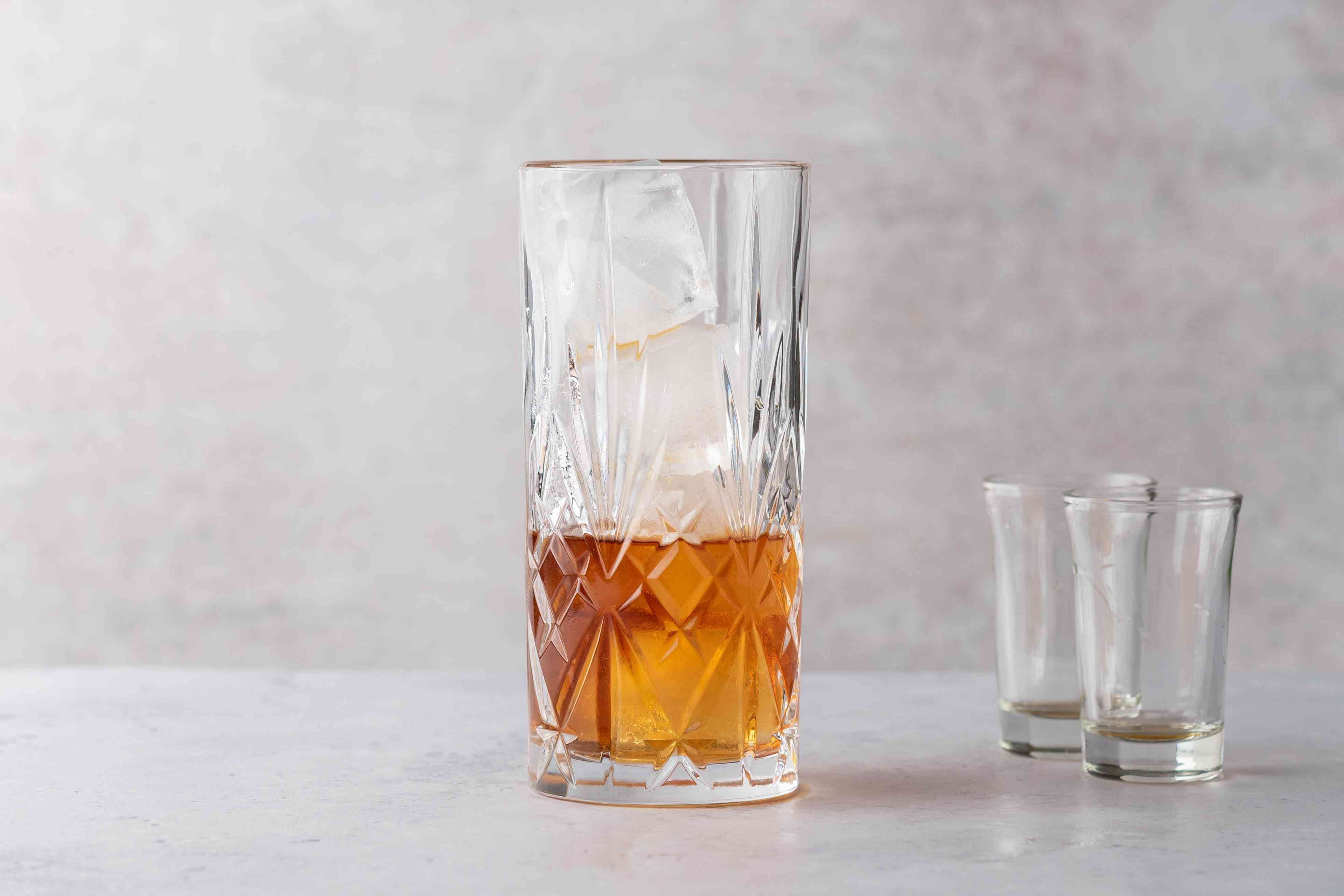 In a collins glass filled with ice, pour the dark rum and amaretto