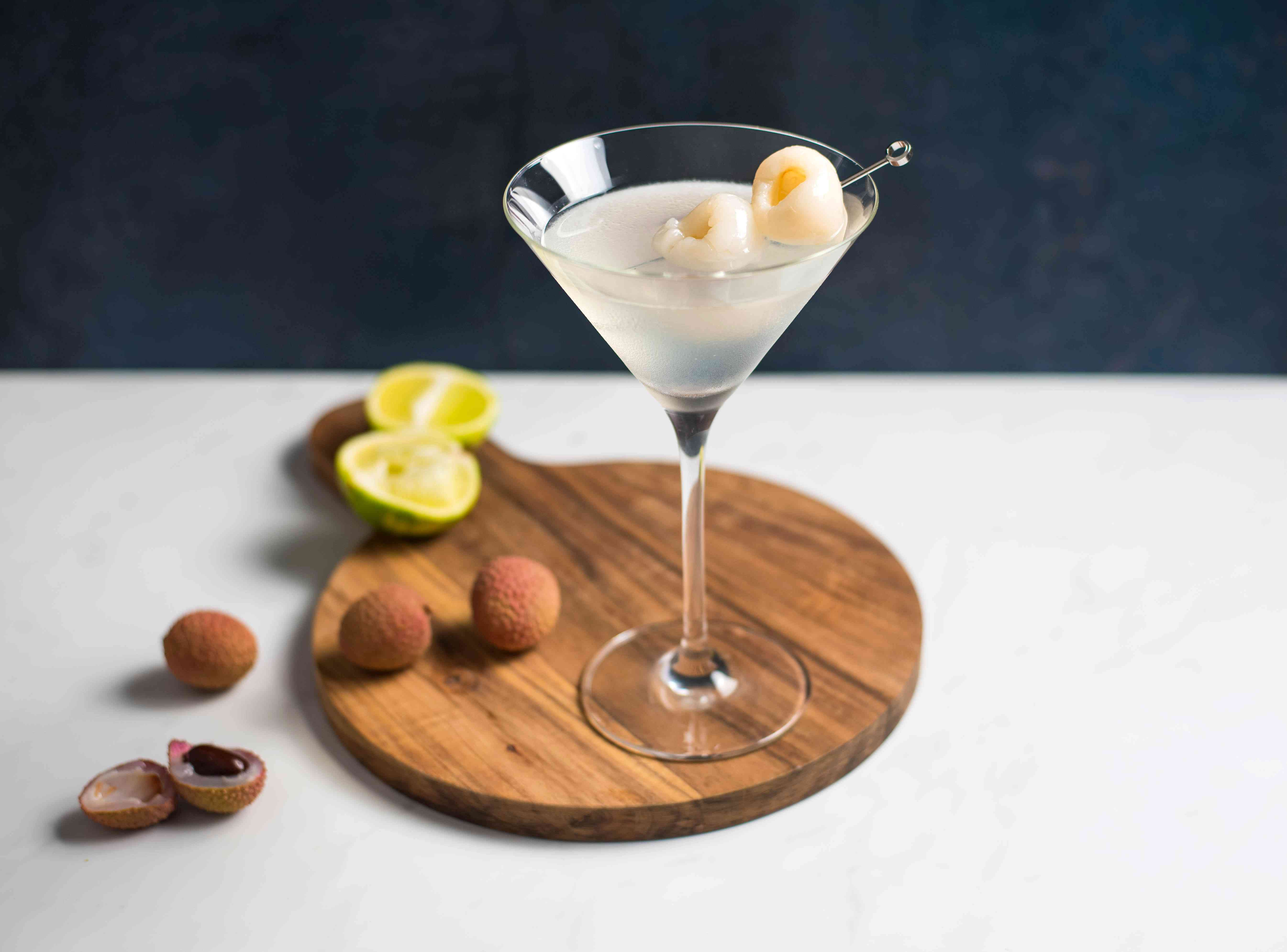 Lychee martini with some scattered lychee fruit and a lime