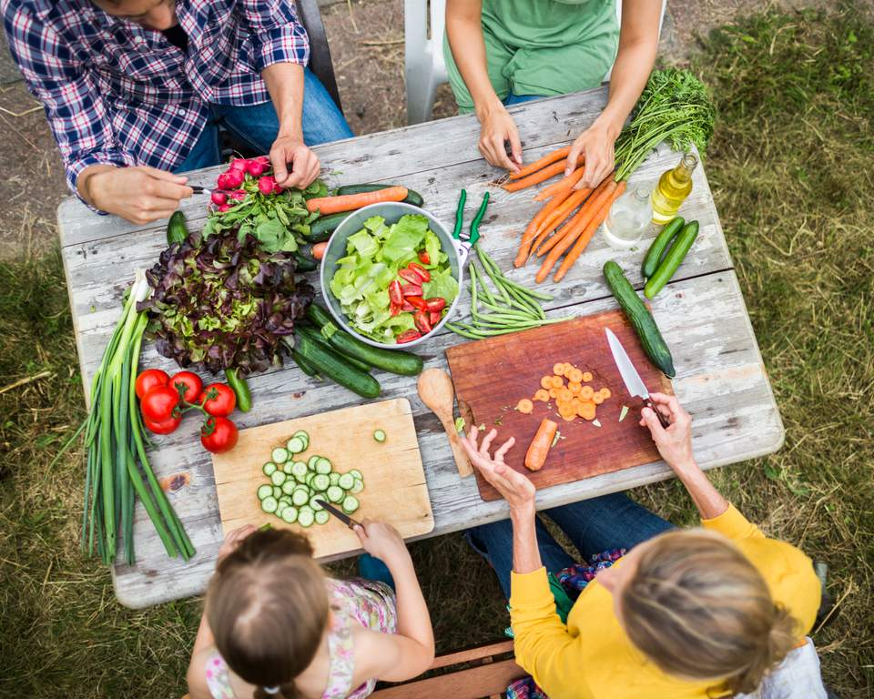 Family Preparing Salad In Garden