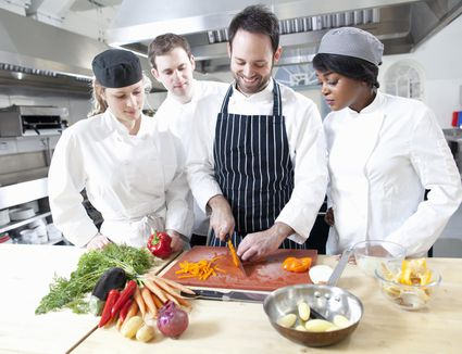A teacher with students in cooking school