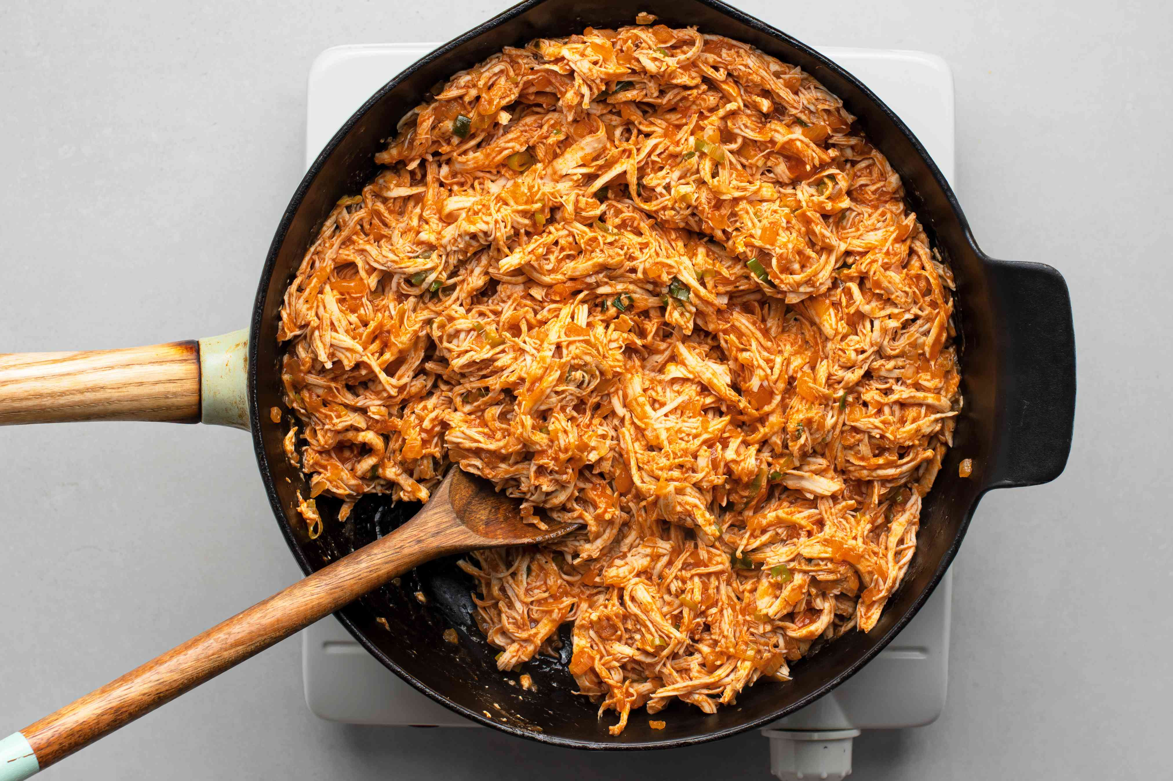 Shredded chicken cooking with the tomato onion mixture in the skillet