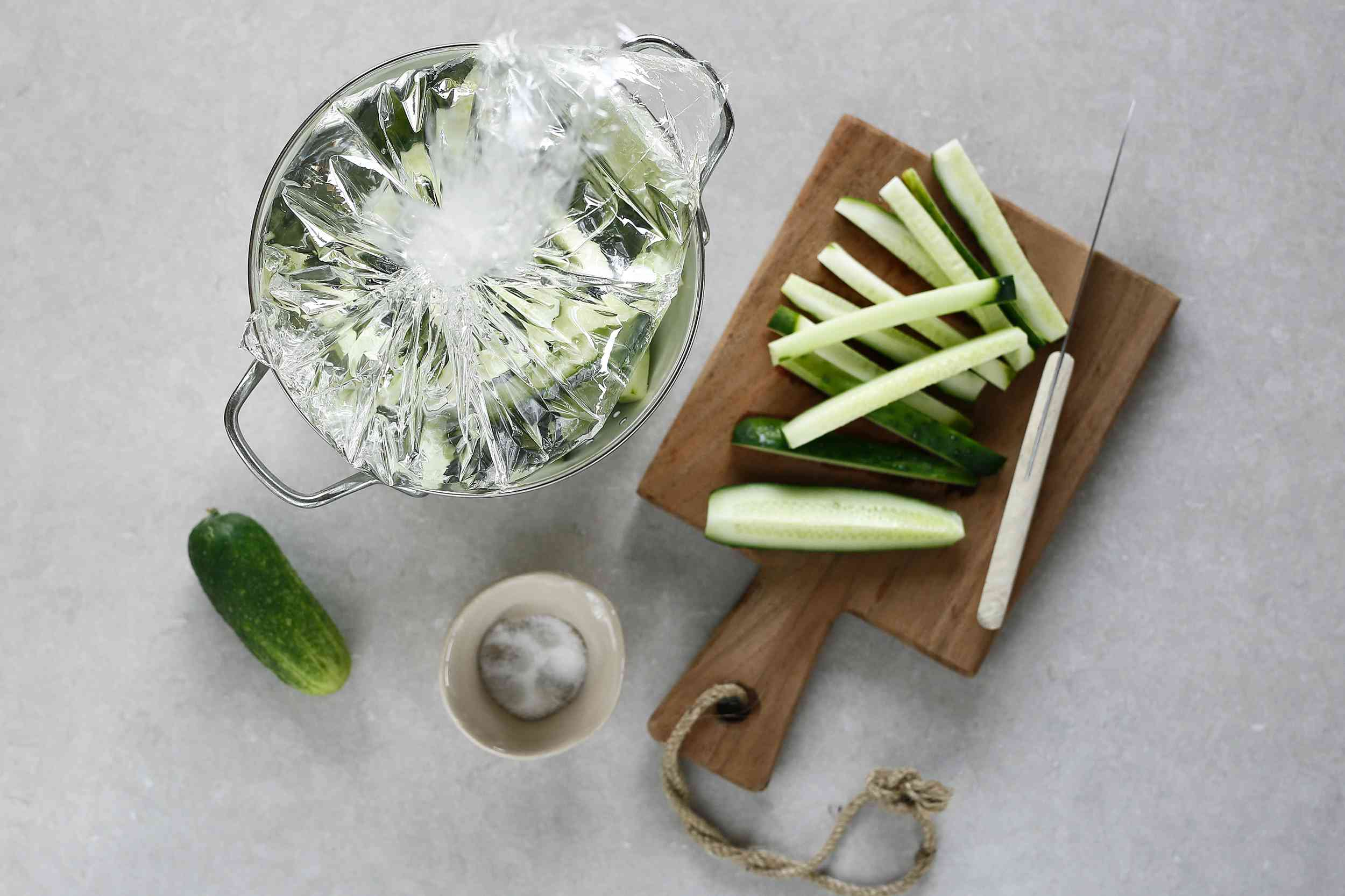cucumber strips on a cutting board, bag of water on top of cucumbers in a colander