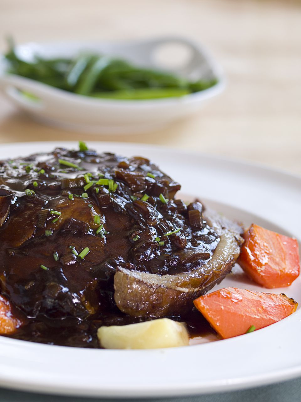 A plate of roast beef with wine sauce and vegetables