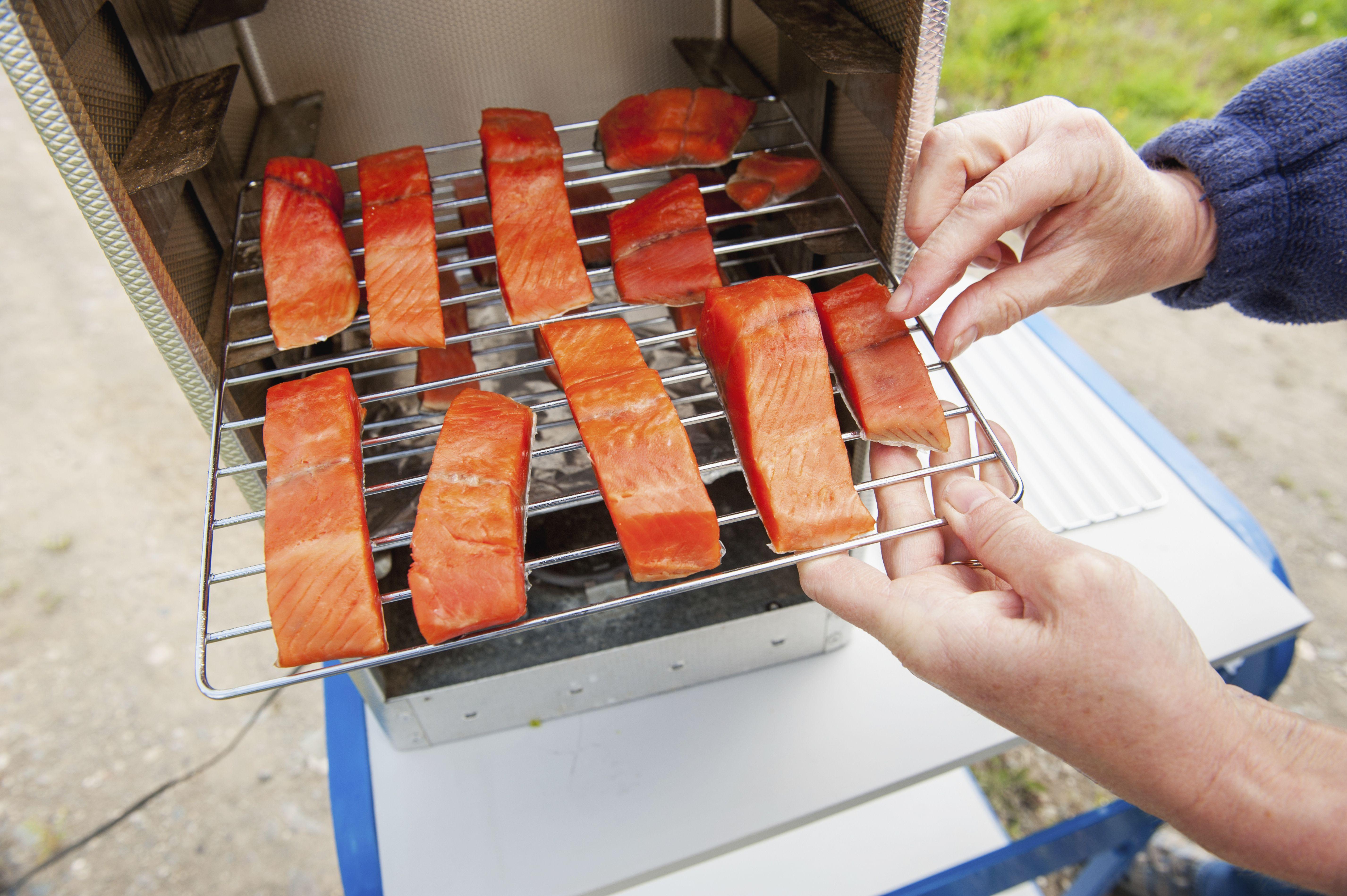Person loading a smoker with prepared salmon, Alaska
