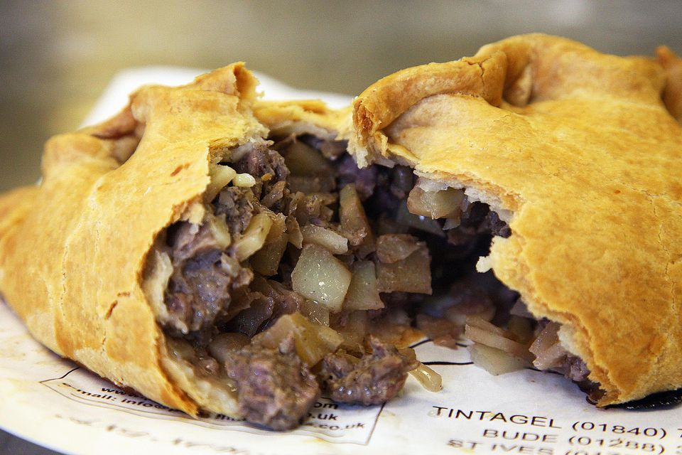 Cornish pasty broken open on newspaper