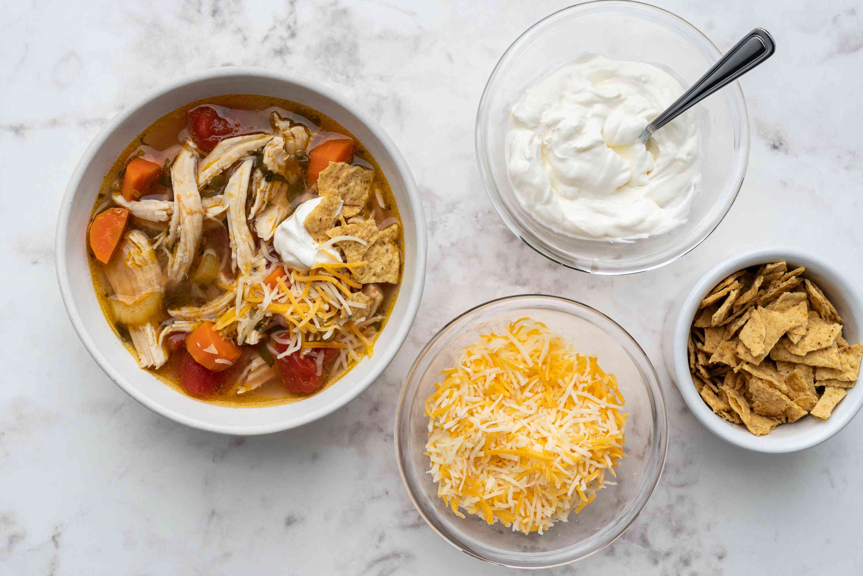 Mexican-Style Shredded Chicken Soup served with cheese, sour cream and chips