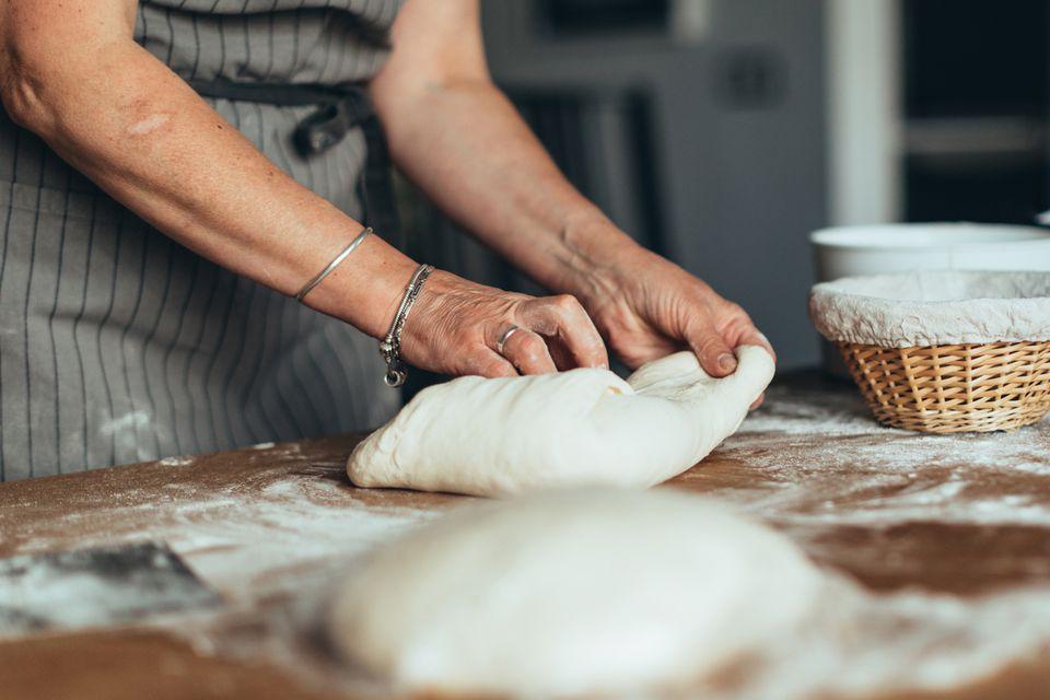 A person folding bread dough.