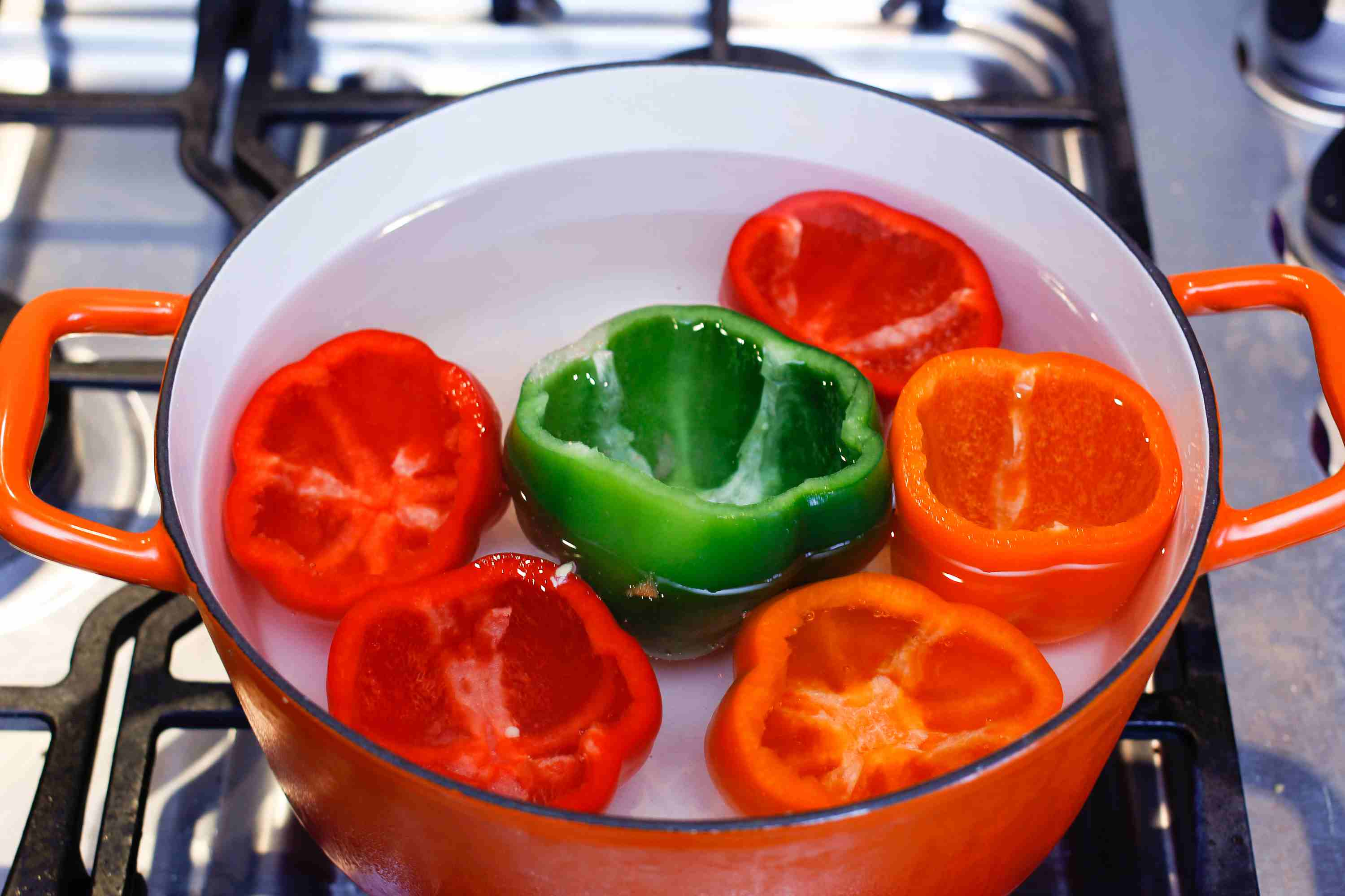 Bell peppers, tops cut off, in a pot of water