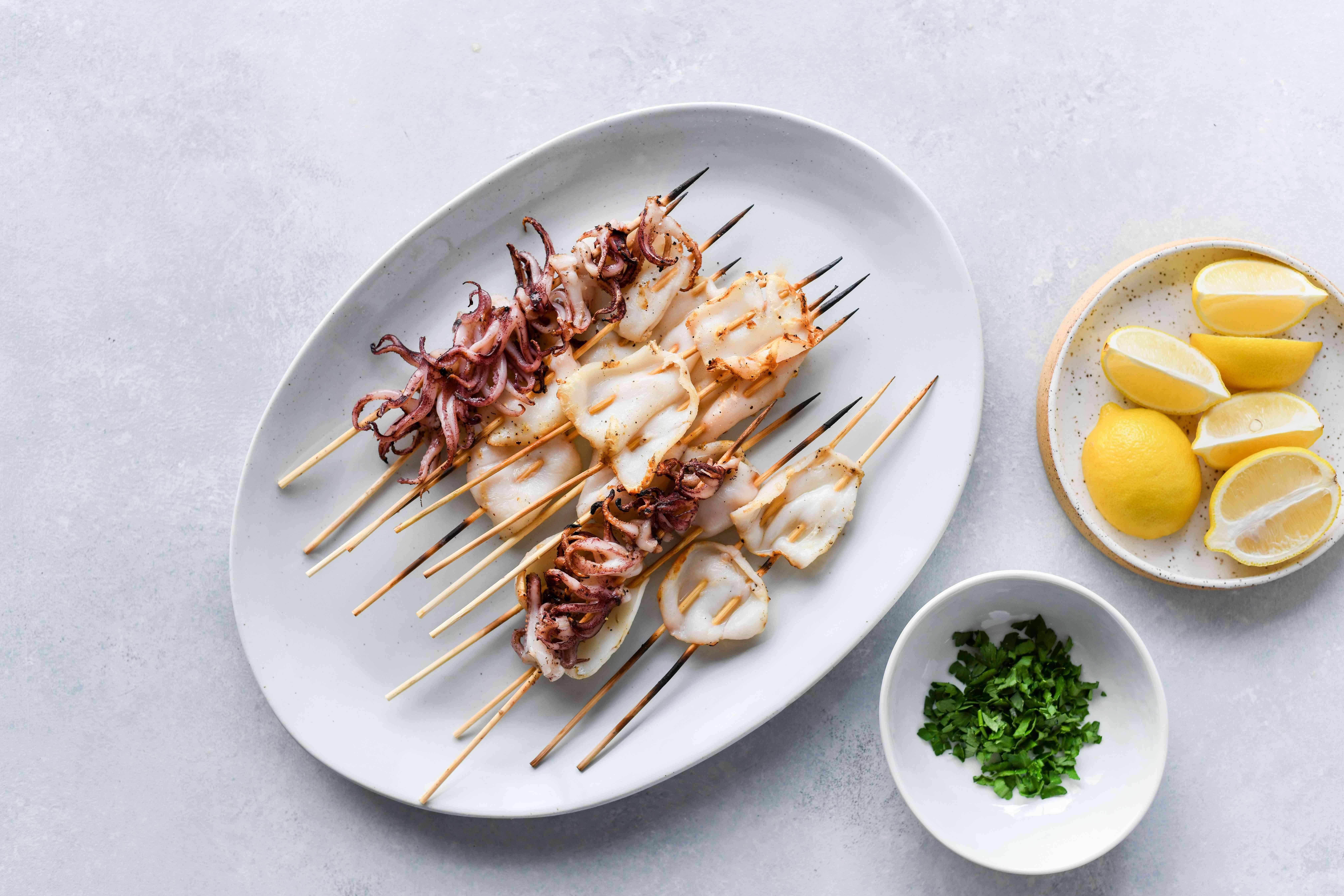 Grilled Squid (Calamari) on a plate, lemon wedges