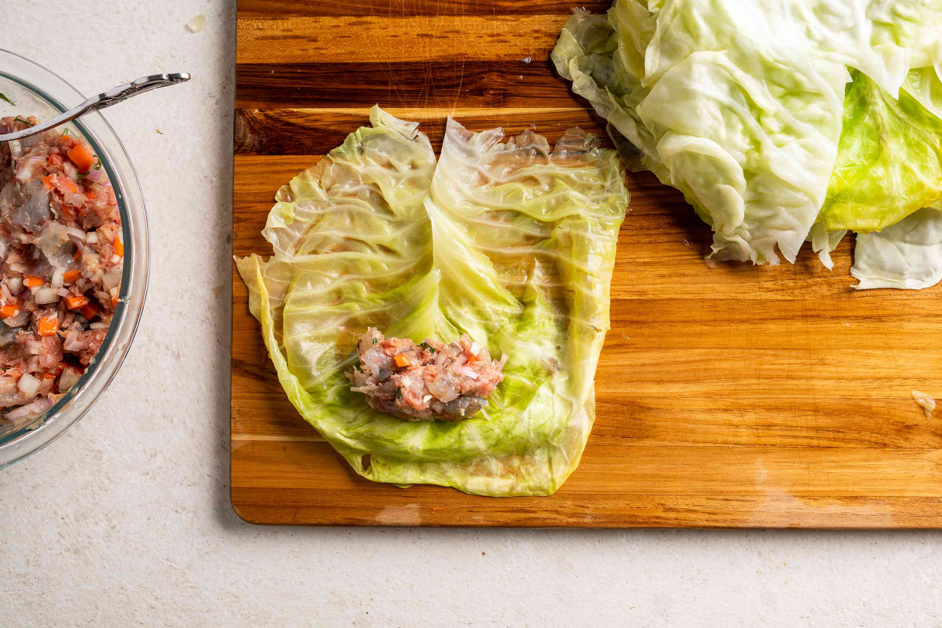 Lay a cabbage roll flat and place filling at the center of the cabbage leaf