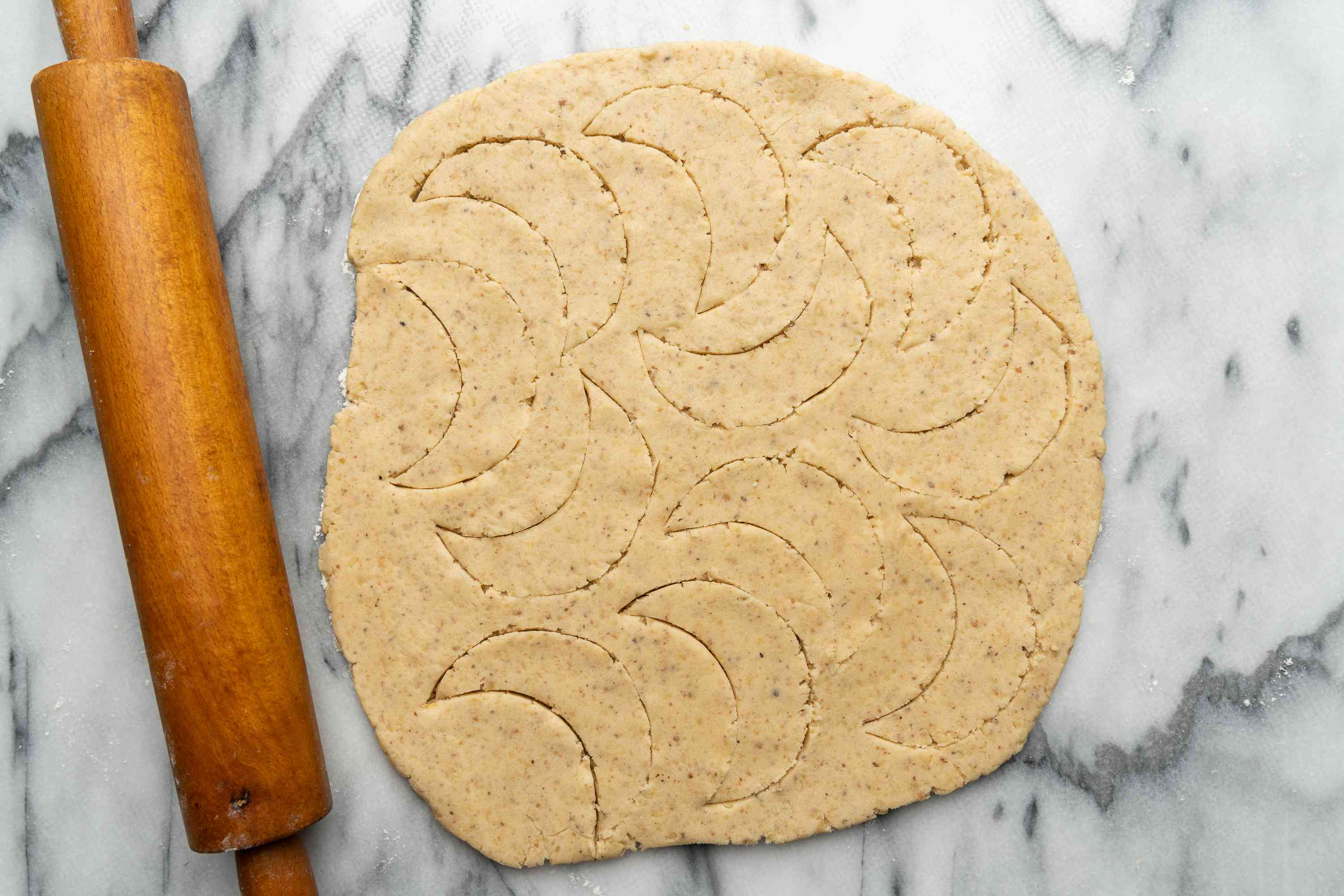 rolled out dough with crescent moon shapes cut out