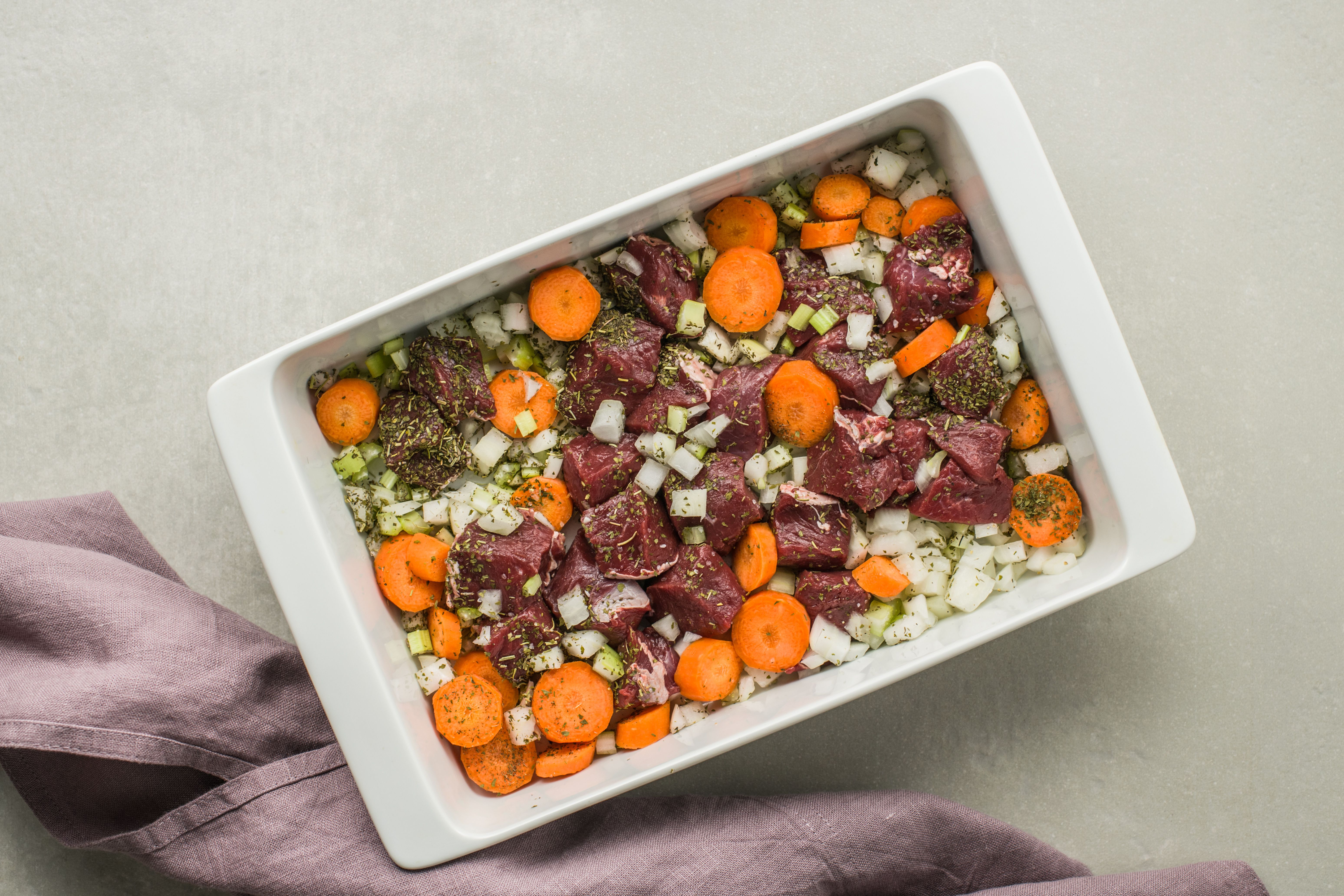Venison, onions, carrots, celery, and seasonings in a casserole dish