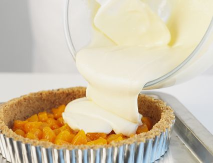 Pouring cheesecake mixture onto oranges