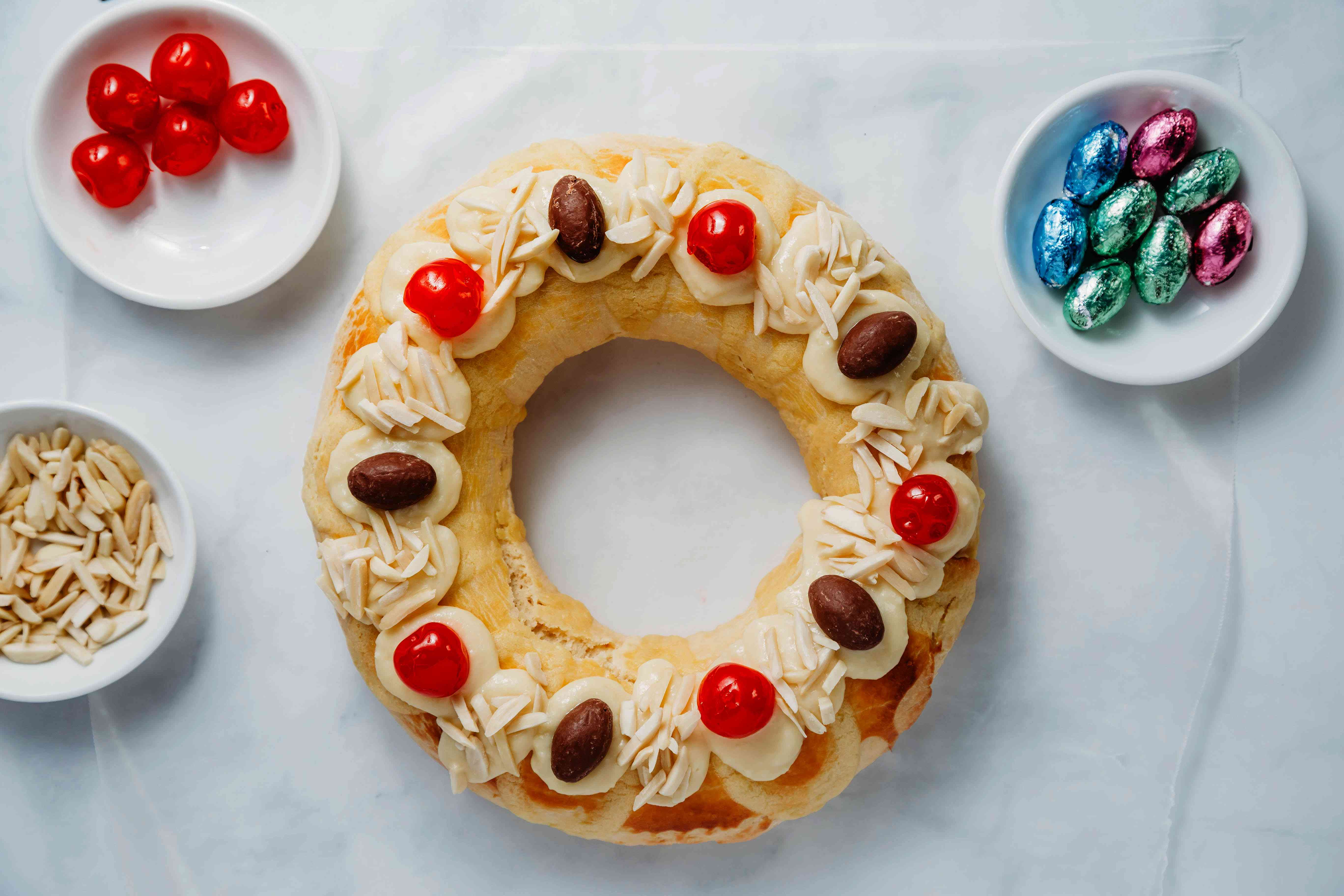 finished cake decorated with more pastry cream, cherries, almonds, candies