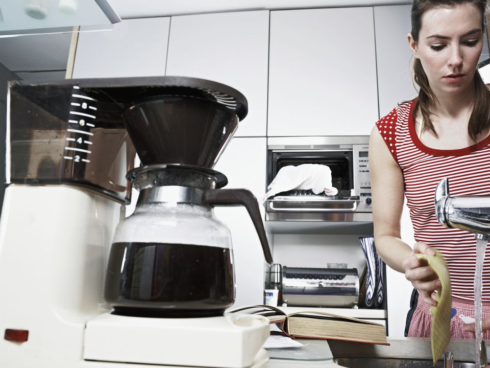 Coffee machine with bean grinder on a table next to a woman