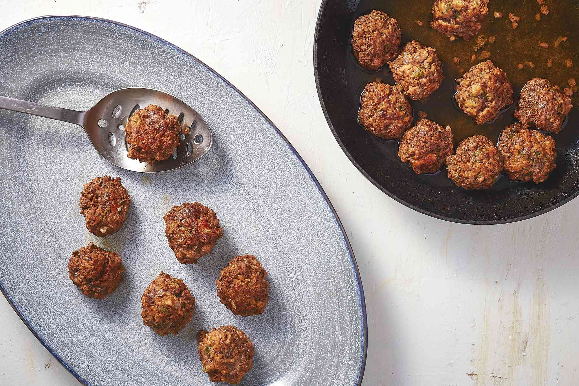meatballs removed from skillet with slotted spoon