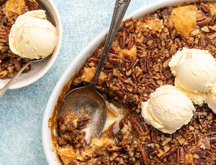 Pecan pie cobbler in a casserole dish with vanilla ice cream