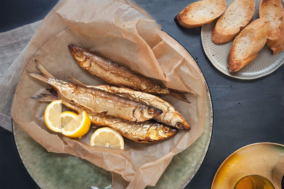 Herring on brown paper with lemon