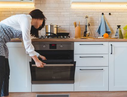 woman using oven in home kitchen