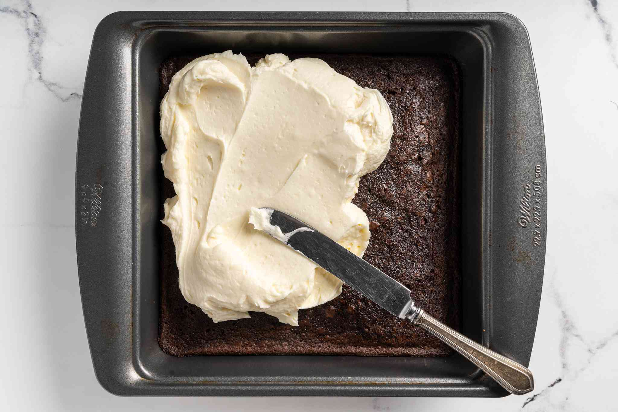 icing spread on top of the brownies in the baking pan