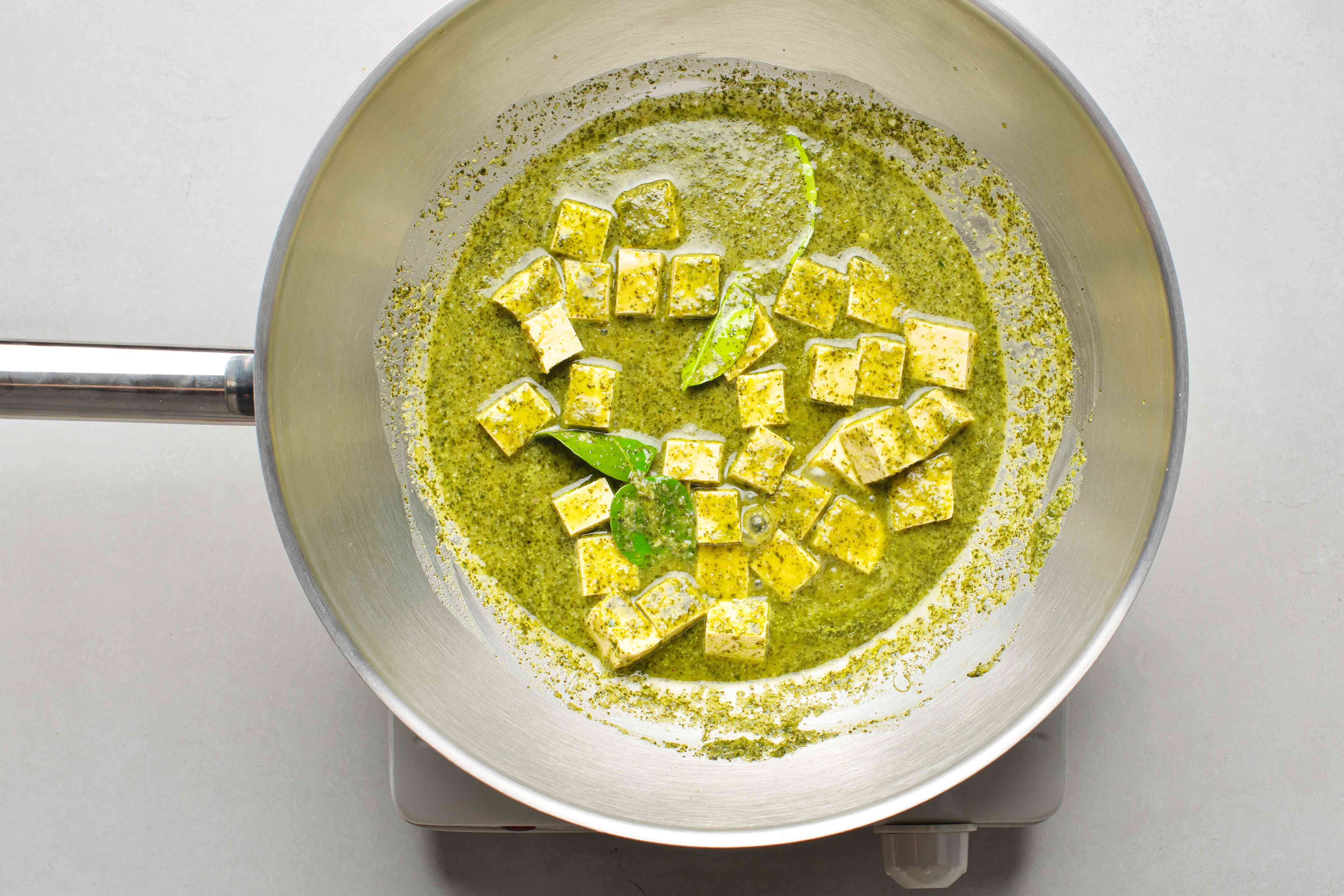 Stock and lime leave added to tofu and green curry in the wok