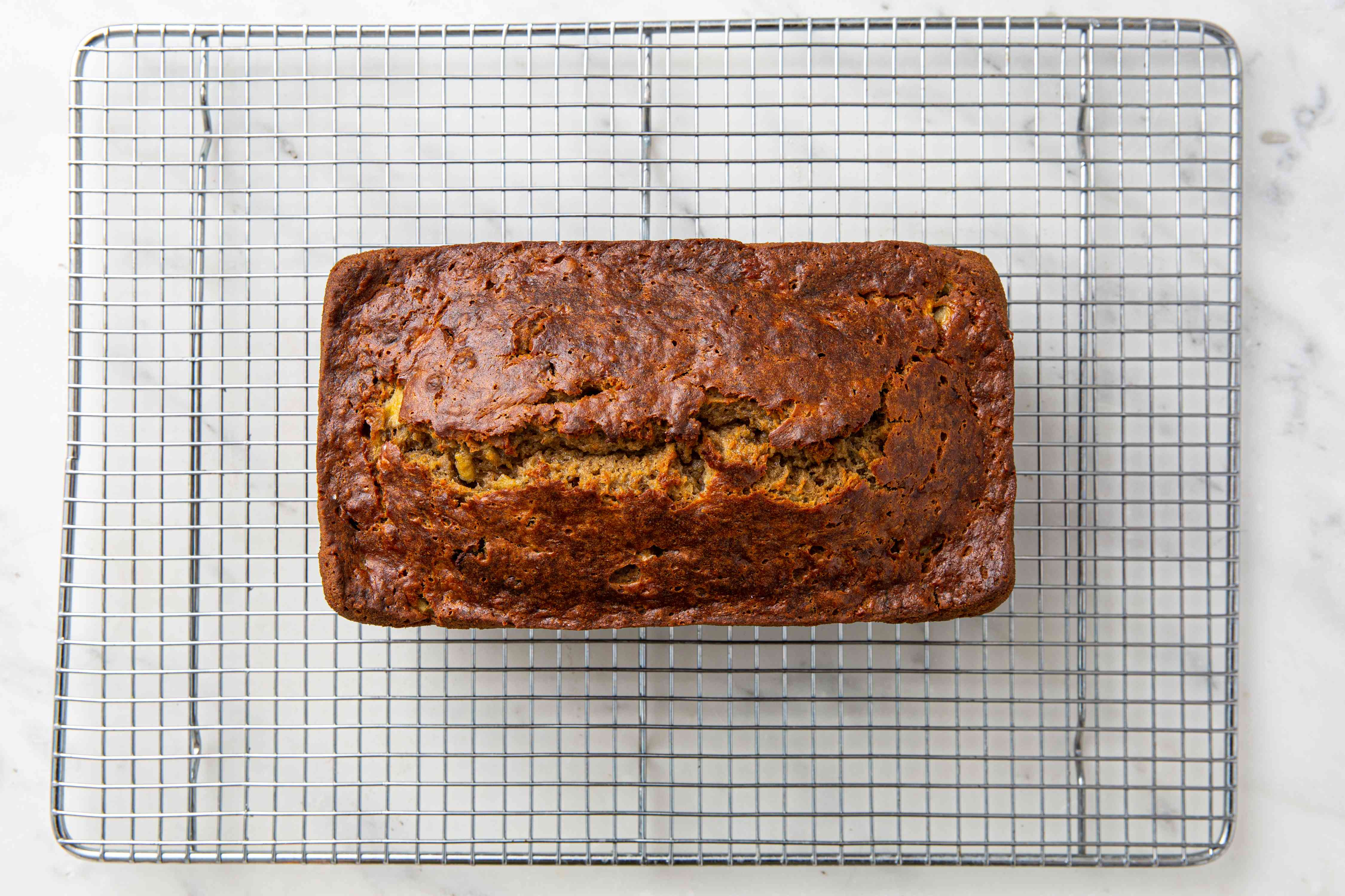 Moist banana bread with coconut oil on a wire cooling rack