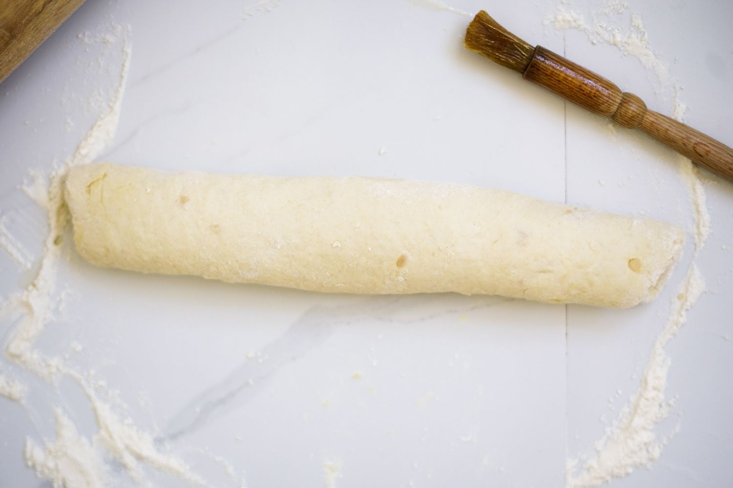 Roti dough rolled out on a marble slab sprinkled with flour