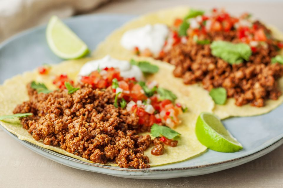 Chorizo tacos with sour cream and lime wedges using homemade mexican-style chorizo
