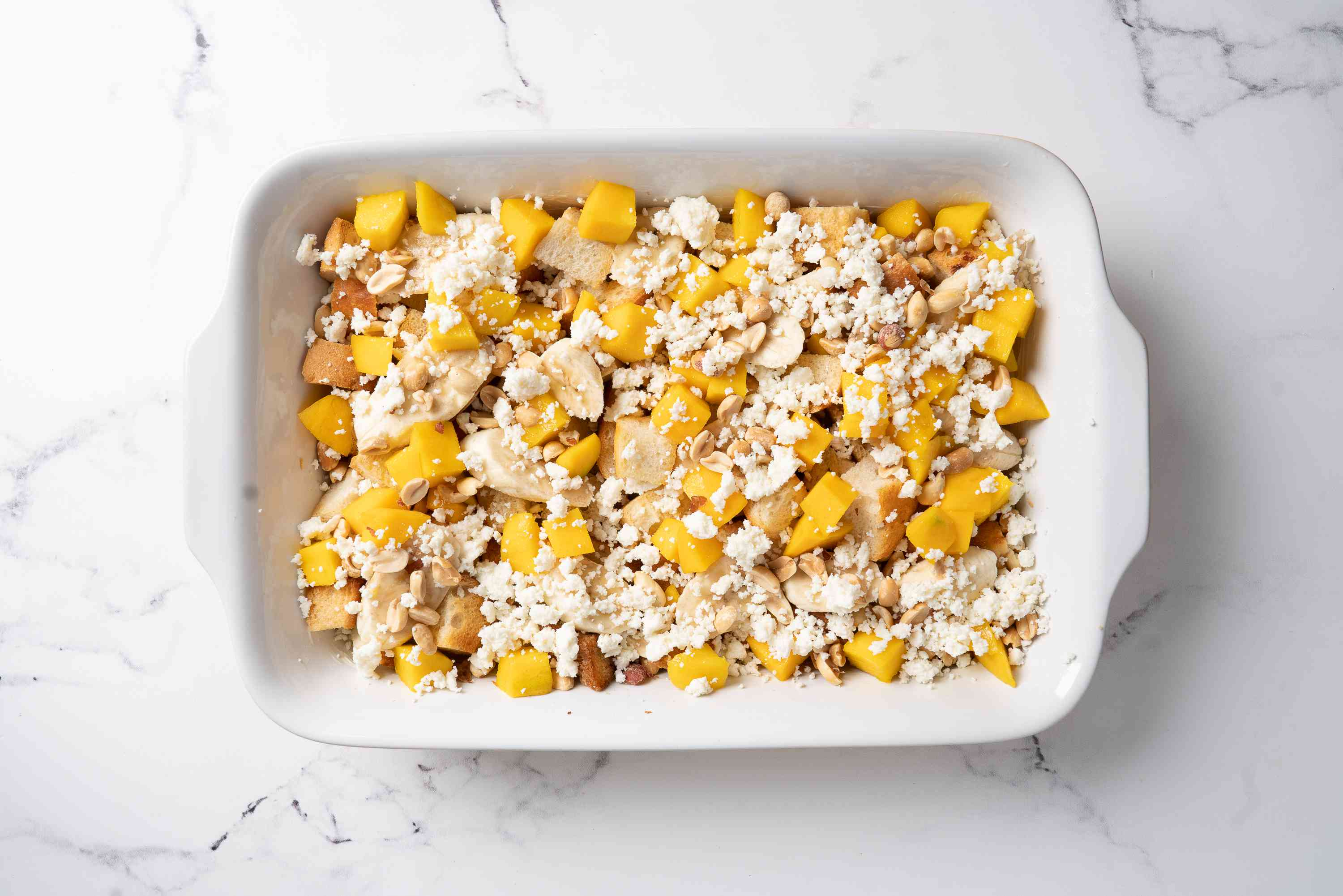 Bread in a casserole dish topped with fruit, cheese, and nuts