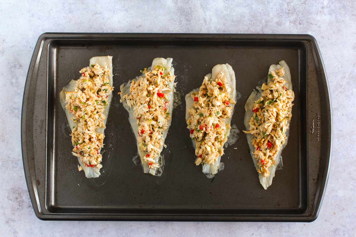 Uncooked stuffed flounder fillets on baking sheet with melted butter