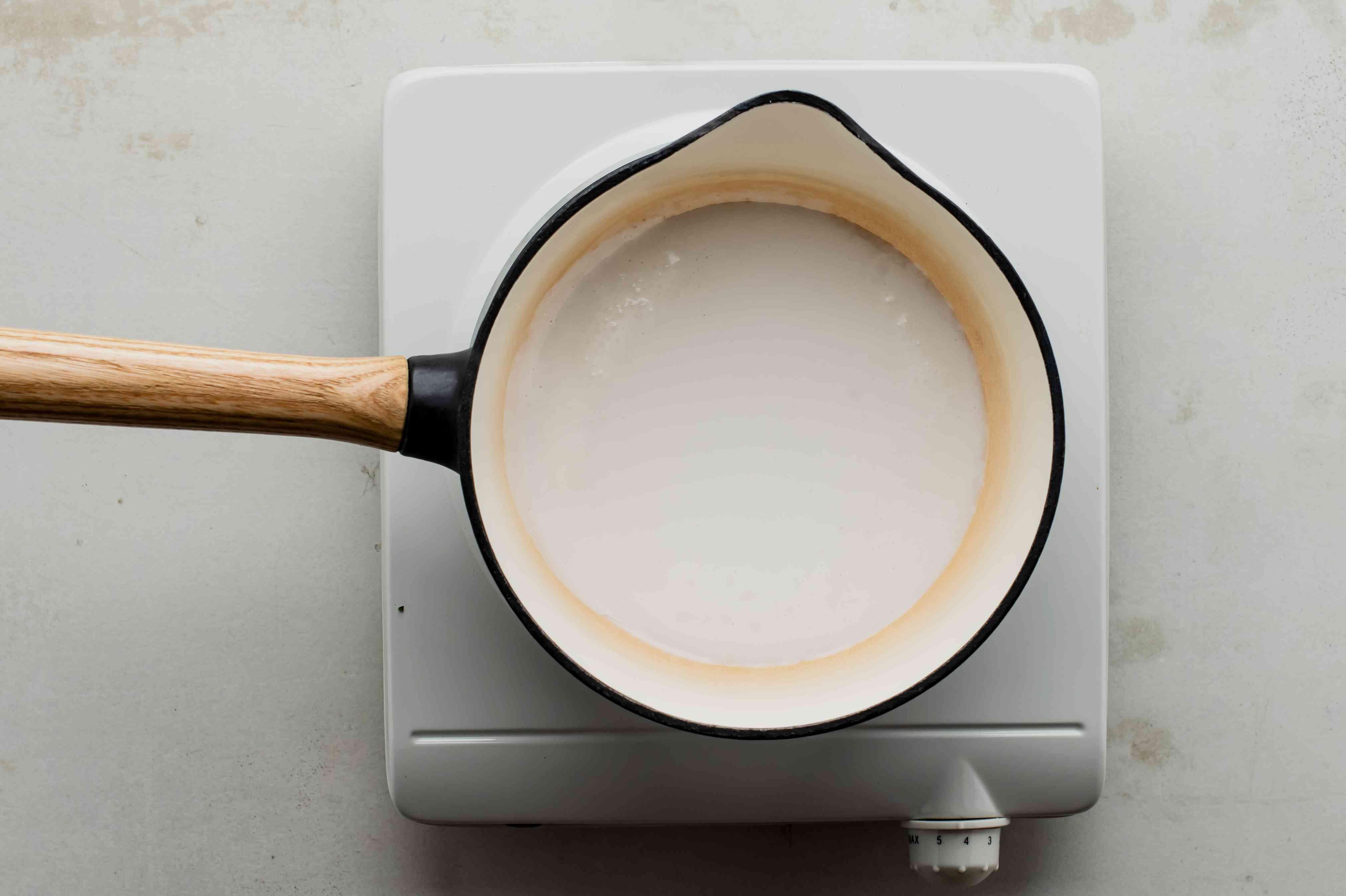 Pour coconut milk into pot