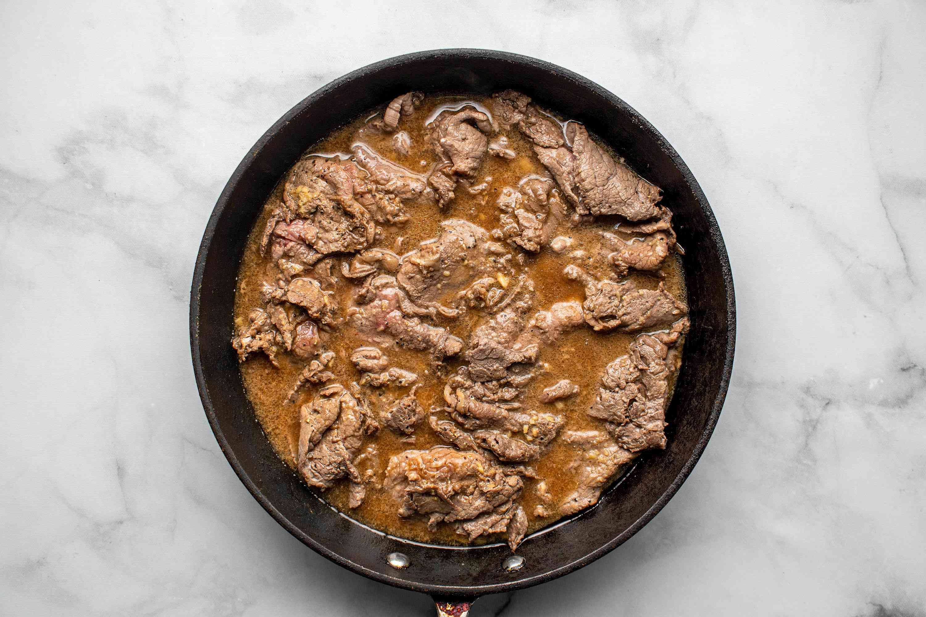 beef cooking in a frying pan