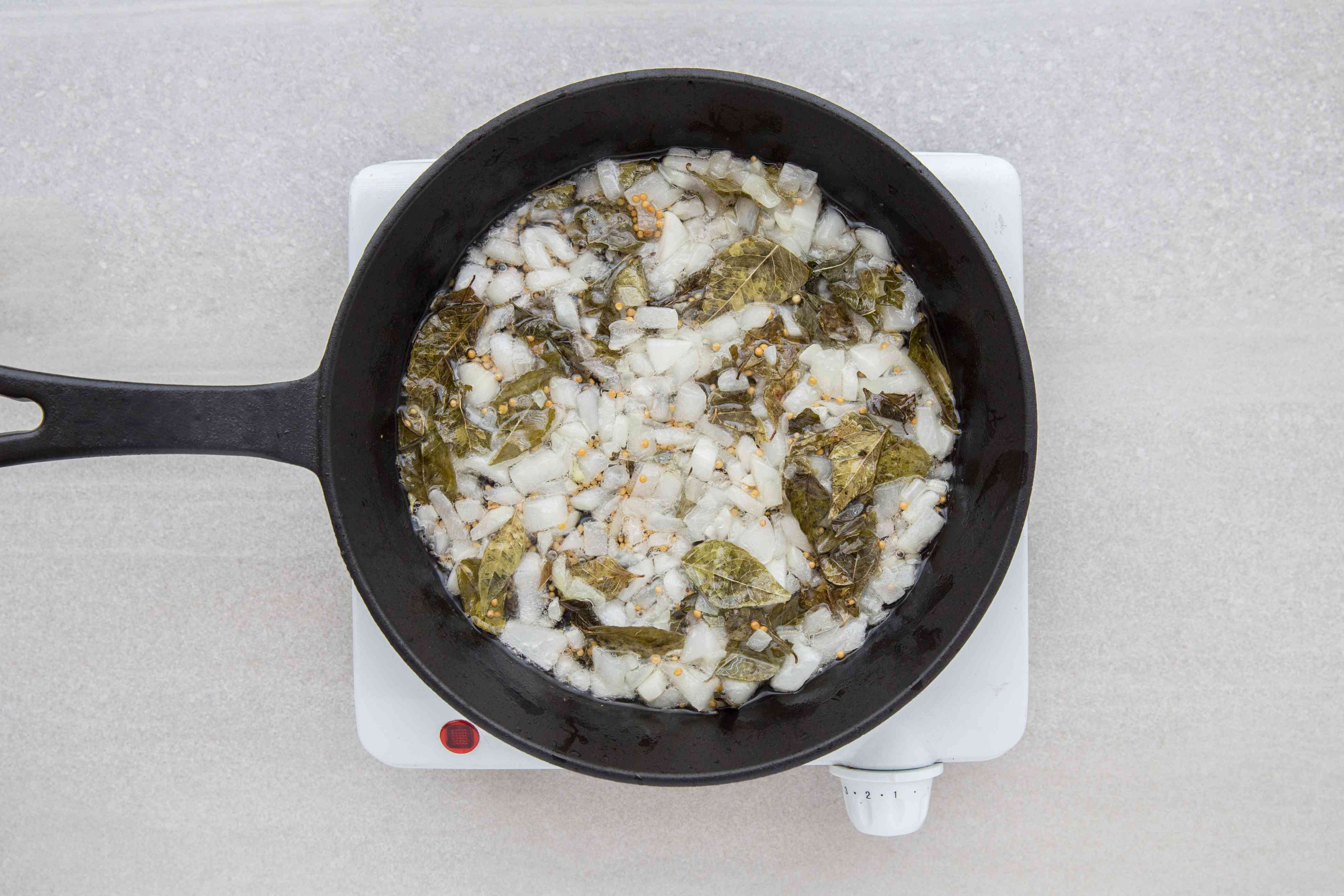 curry leaves and mustard seeds in a pan with onions