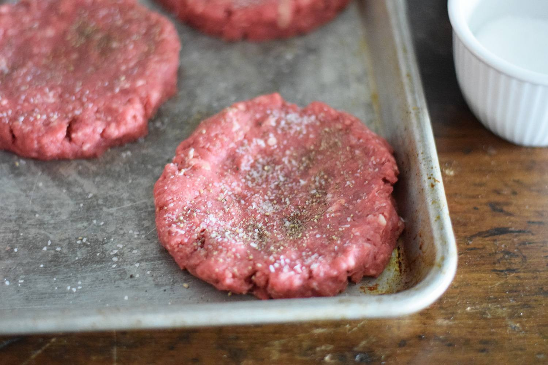 Seasoning the hamburger patties