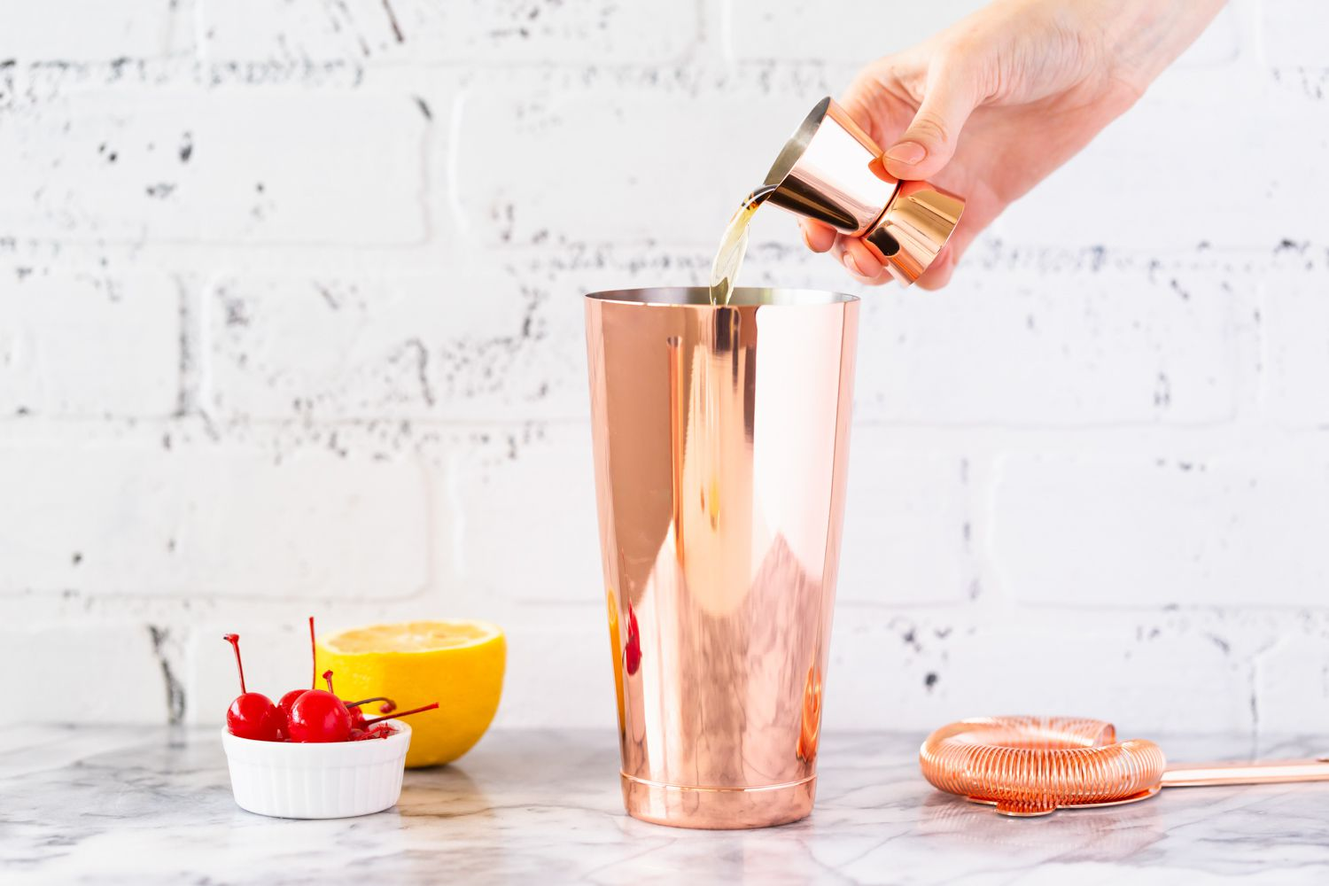 Adding ingredients to a whiskey sour in cocktail shaker