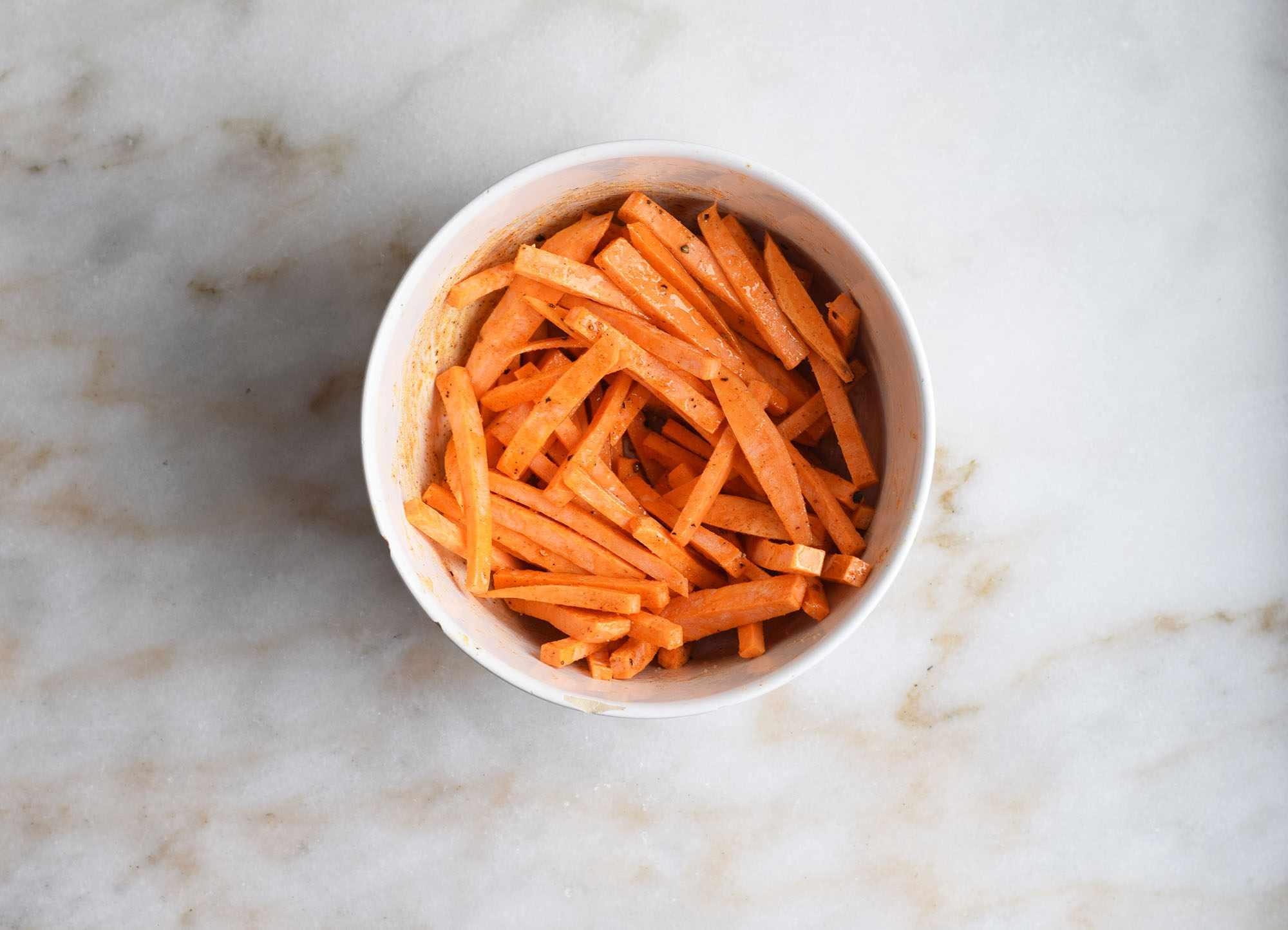 Sweet potato fries coated in oil and seasonings