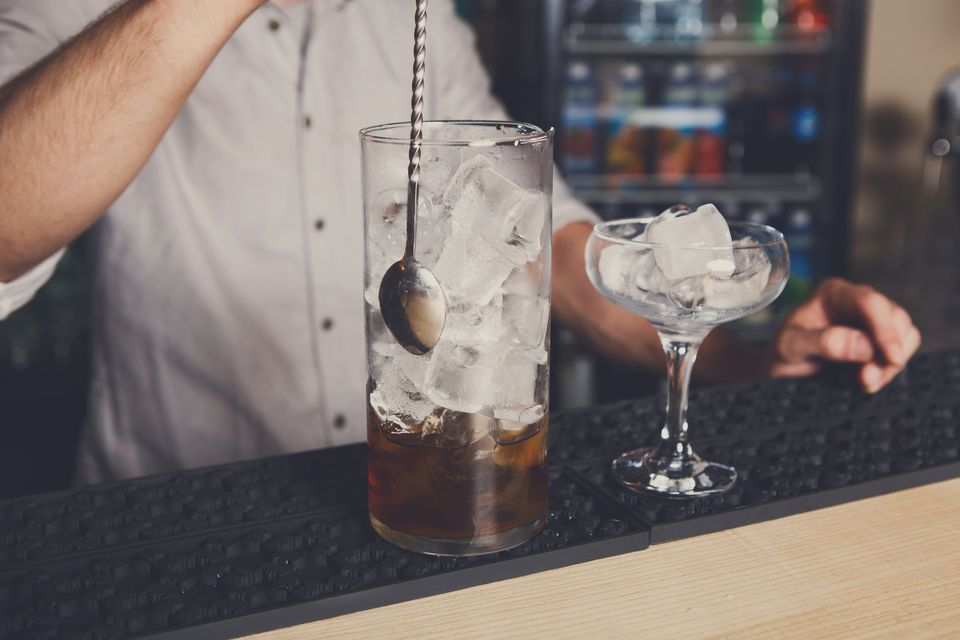 Young male bartender mixing cocktail in an ice-filled pitcher, while a glass chills, full of ice.