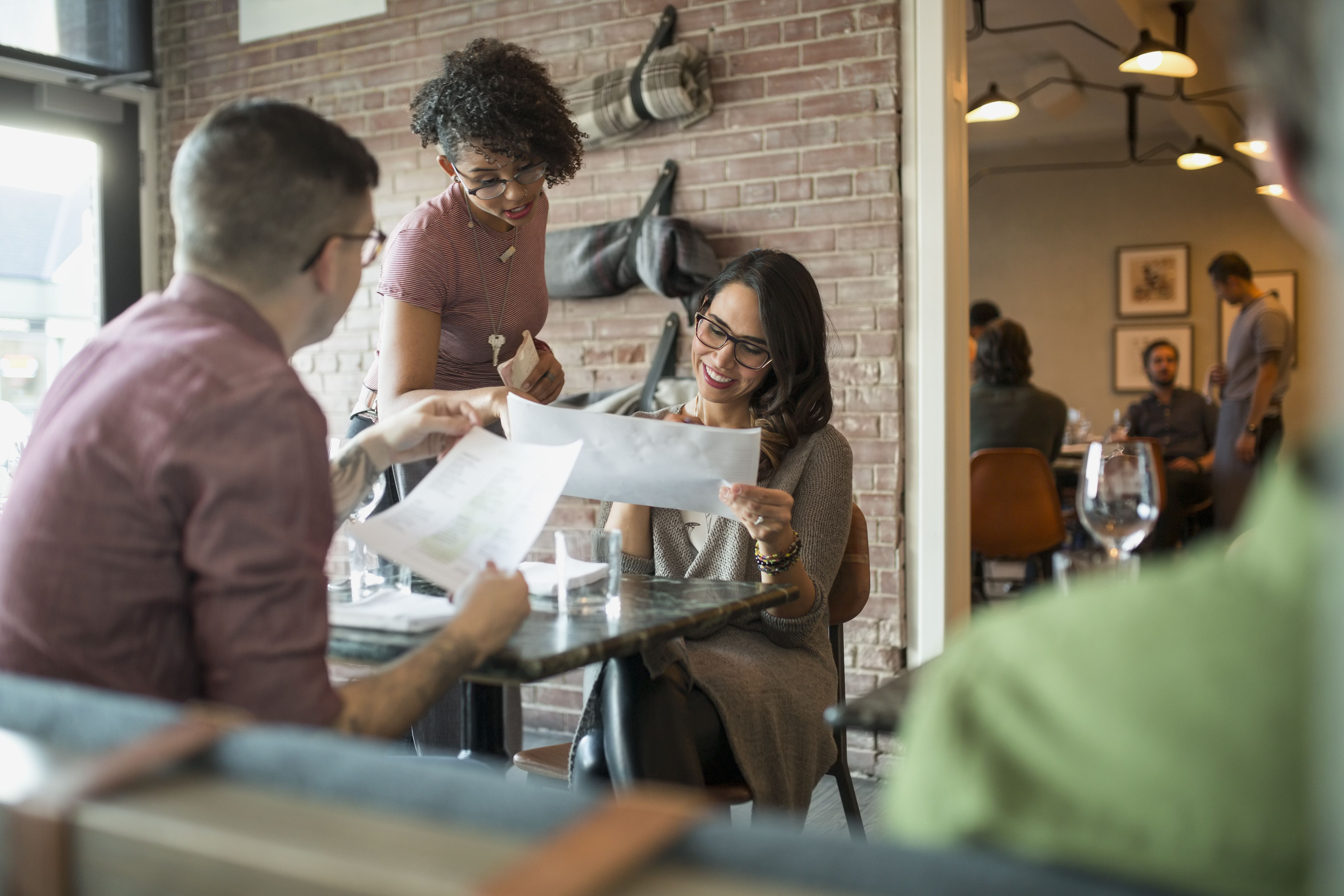 Waitress taking order from couple at restaurant table