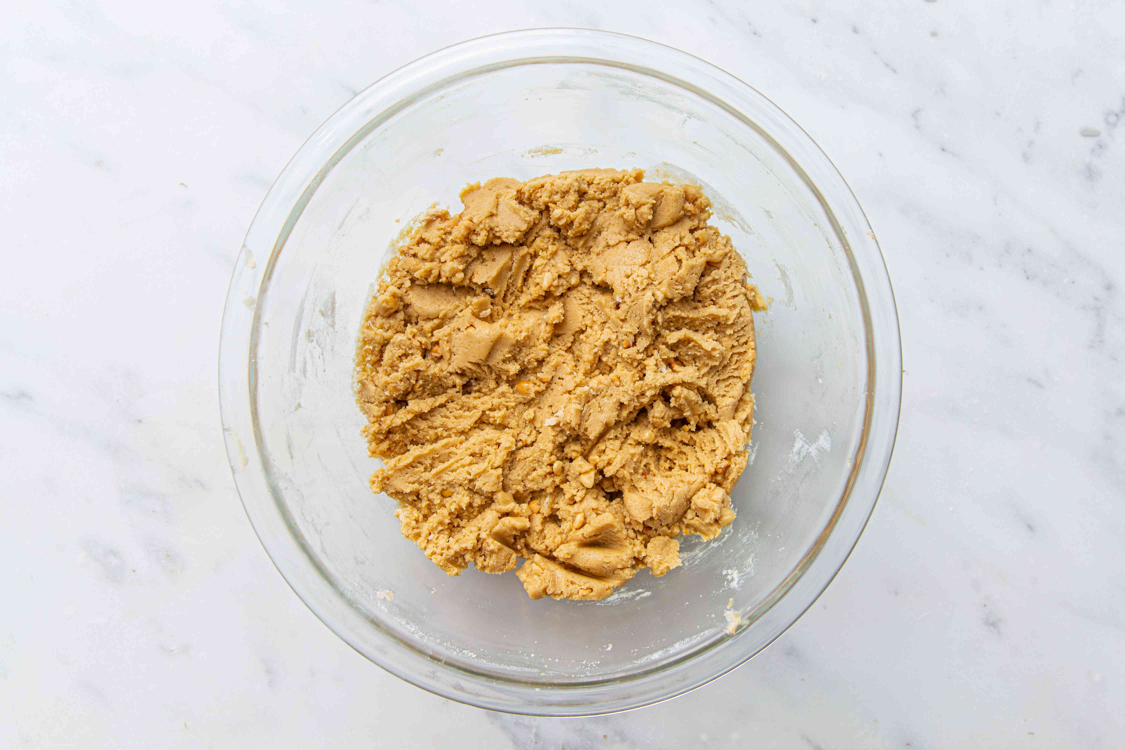 Flour mixture and creamed peanut butter mixture combined together in a large glass bowl