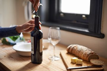 Someone opening a wine bottle by a cheese and bread board