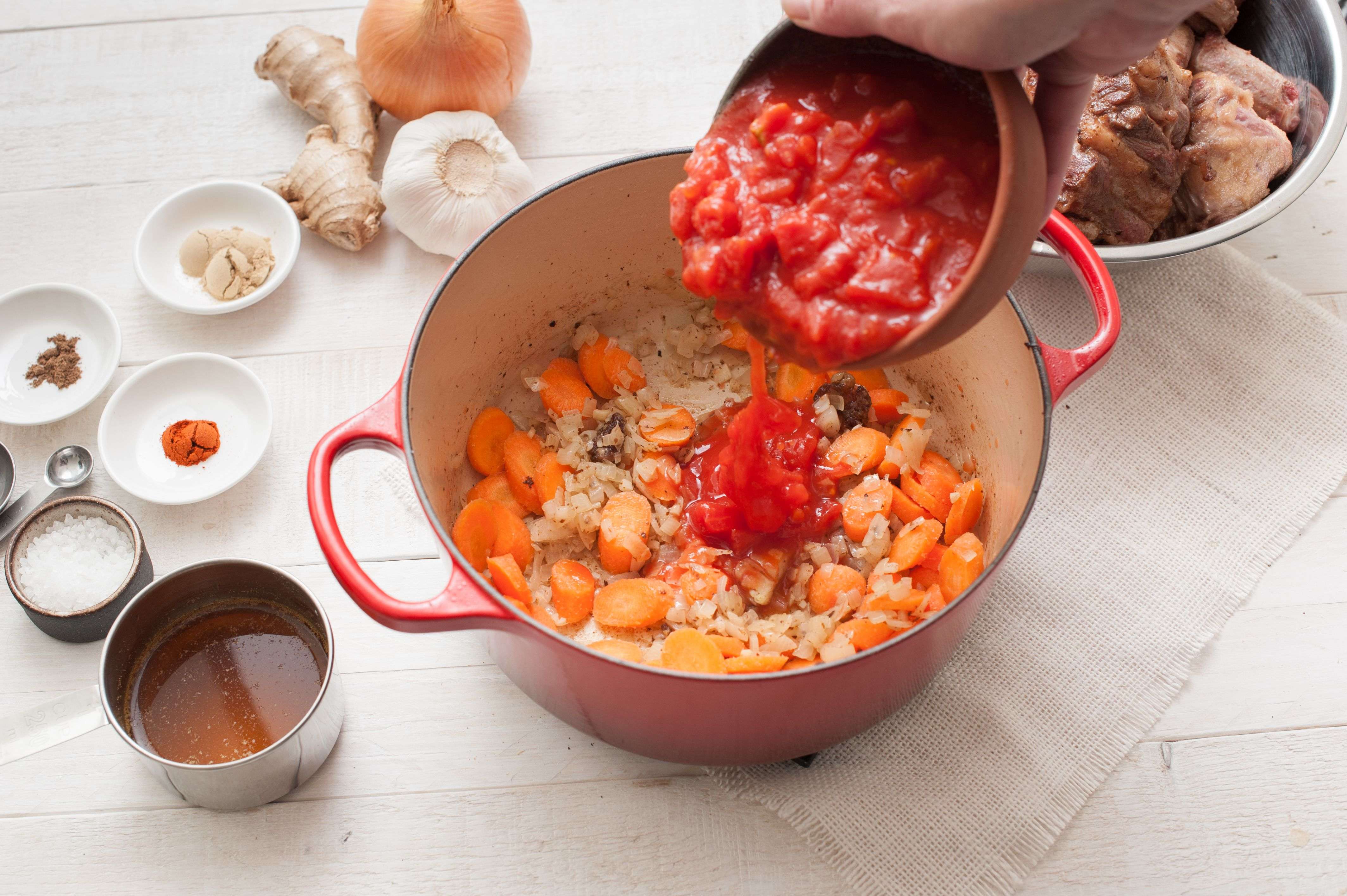 Carrots and tomatoes in Dutch oven with chopped onion