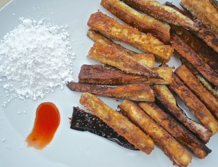 Crispy eggplant sticks on a white plate with hot sauce and powdered sugar