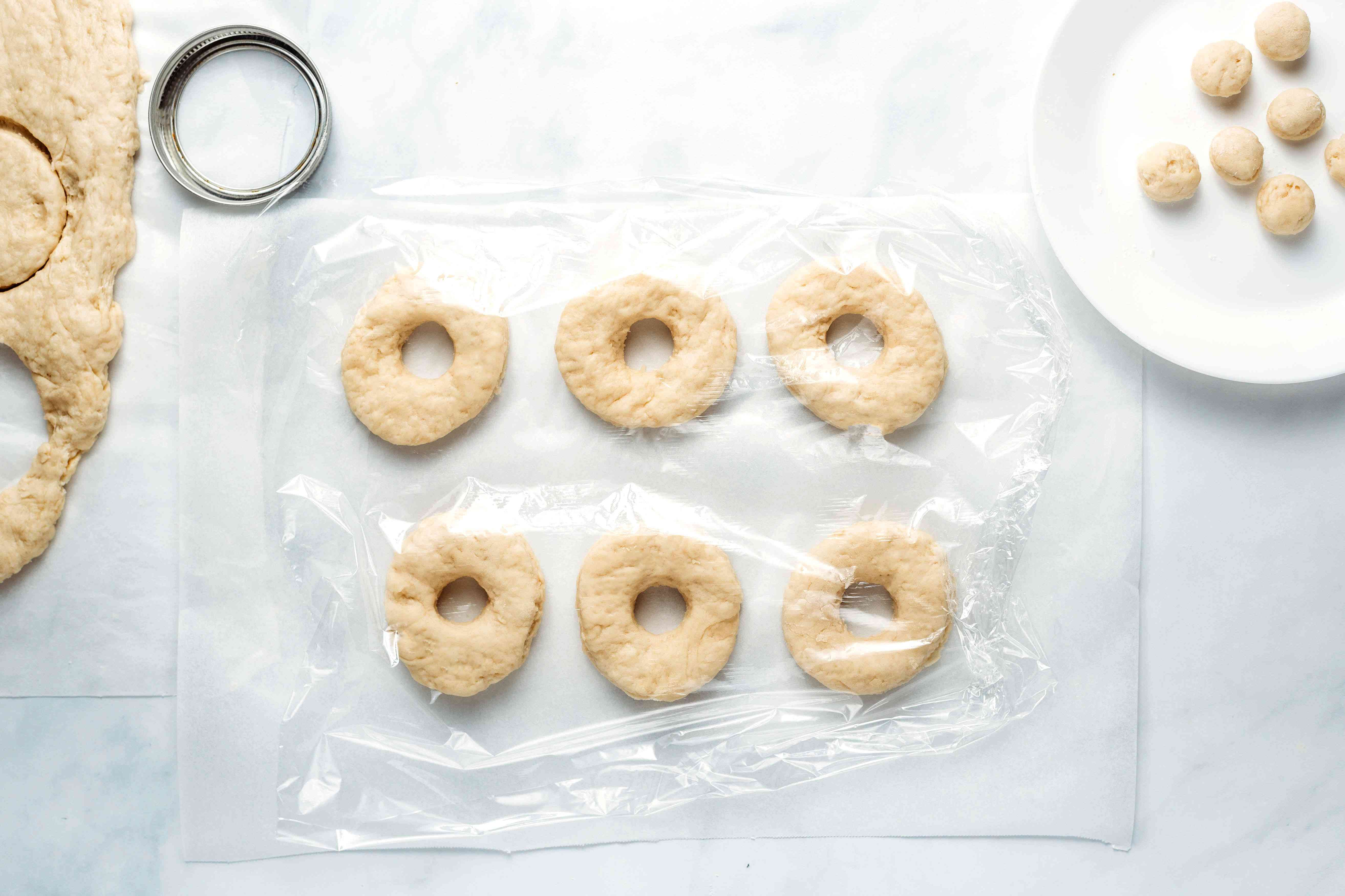 Cronut Dough shaped into donut shapes, on parchment paper covered in plastic wrap