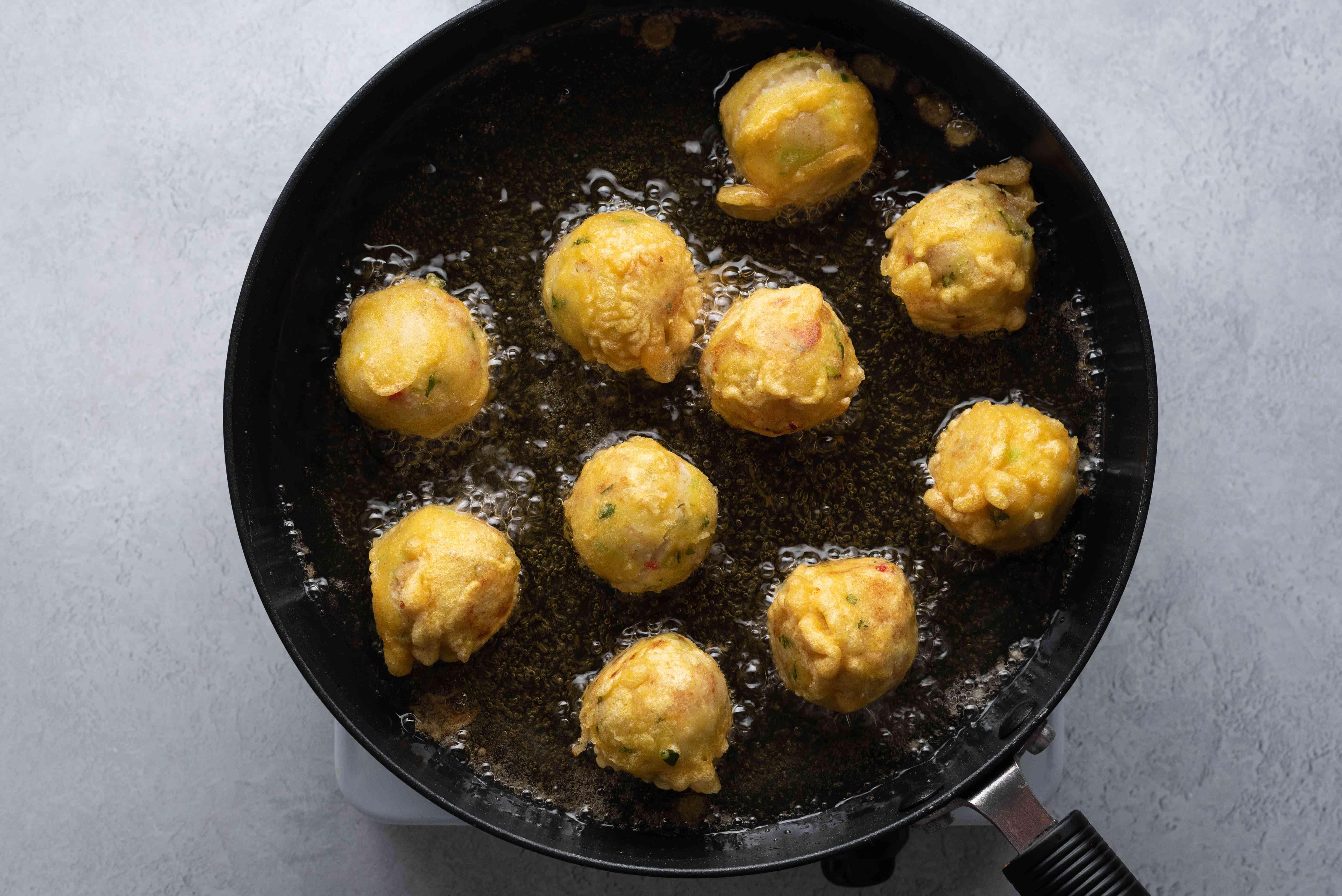 A pan of battered mashed potato balls frying