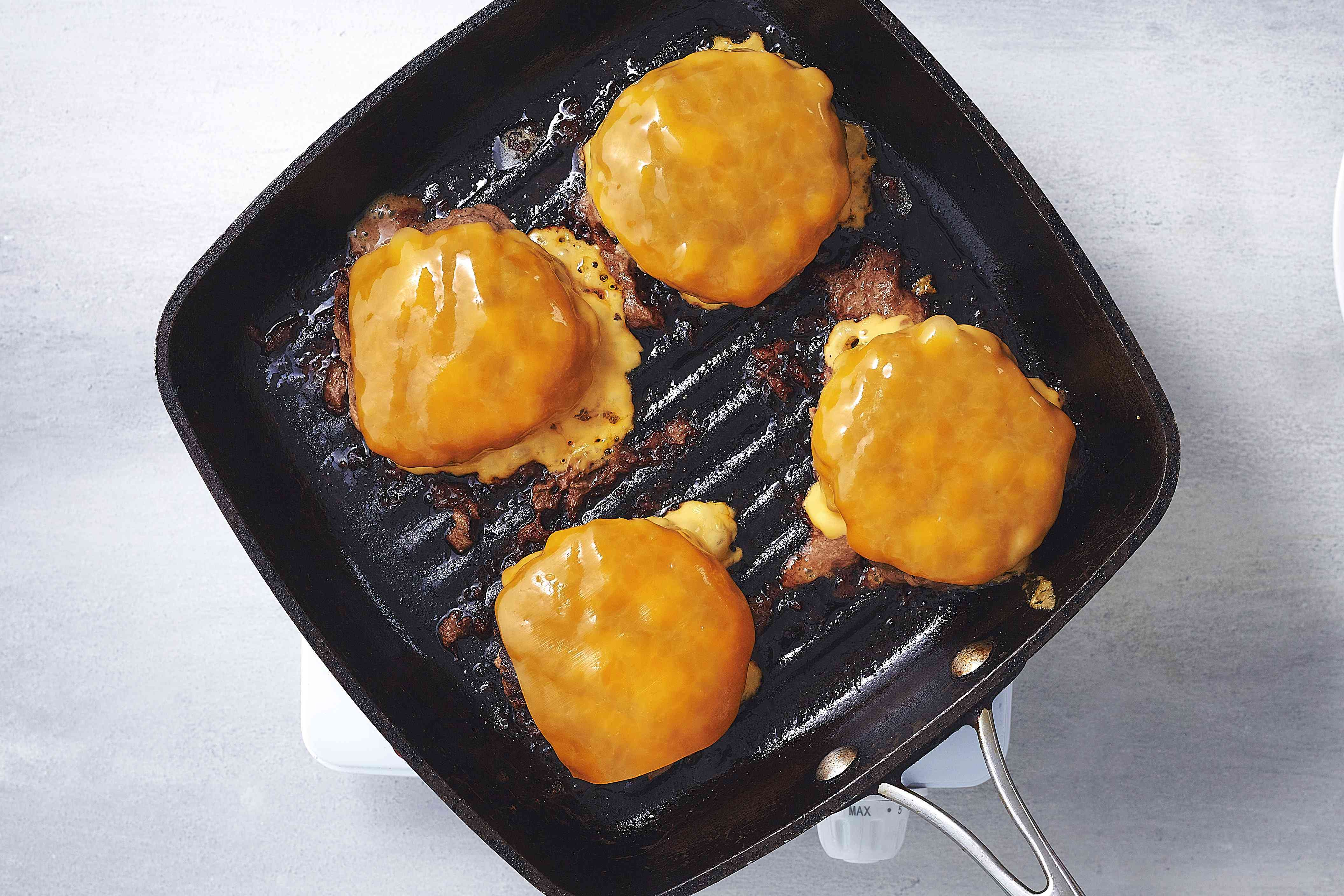 burger patties with cheese on a grill pan