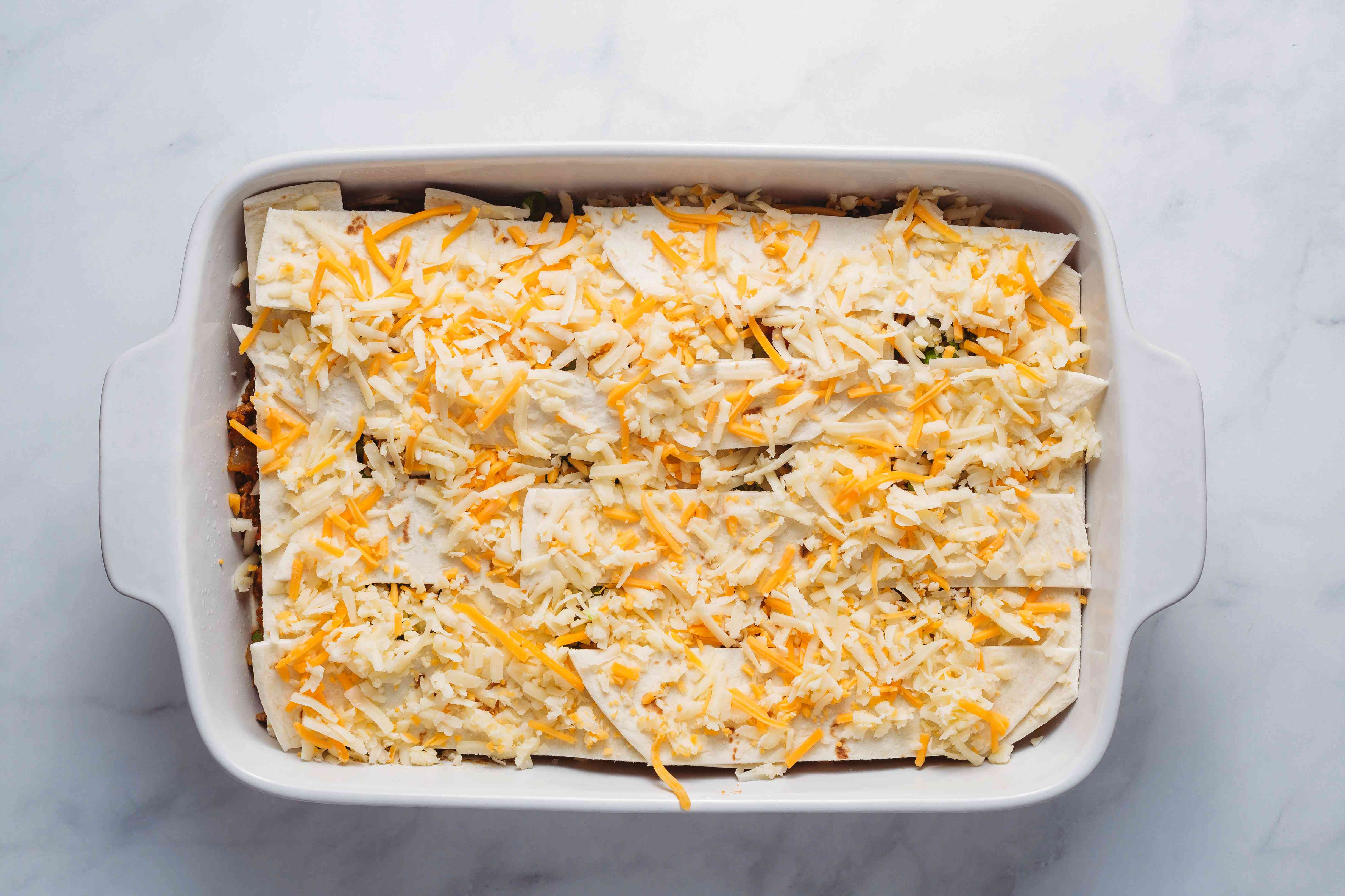 burrito casserole topped with tortillas and cheese
