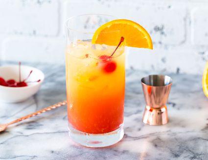 Tequila sunrise with a maraschino cherry and orange slice