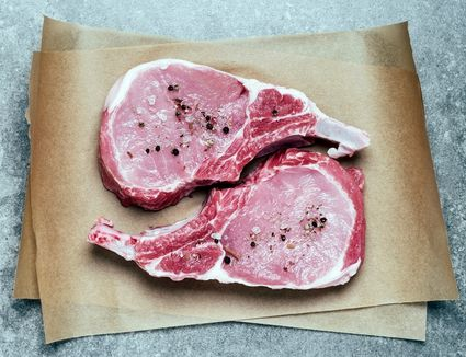 Raw pork chops with salt and pepper