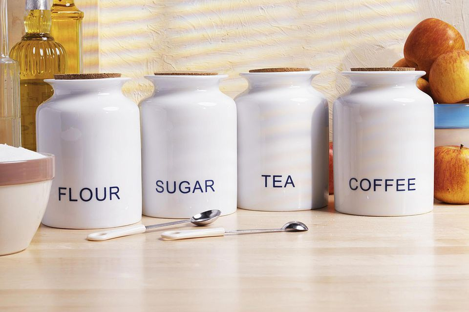 Flour, sugar, tea and coffee canisters on a wooden counter with measuring spoons